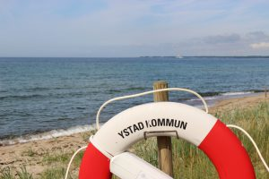 Lifebelt in front of the Baltic sea. The label on the lifebelt says: Kommune of Ystad. Ystad is film location of the crime series Wallander.